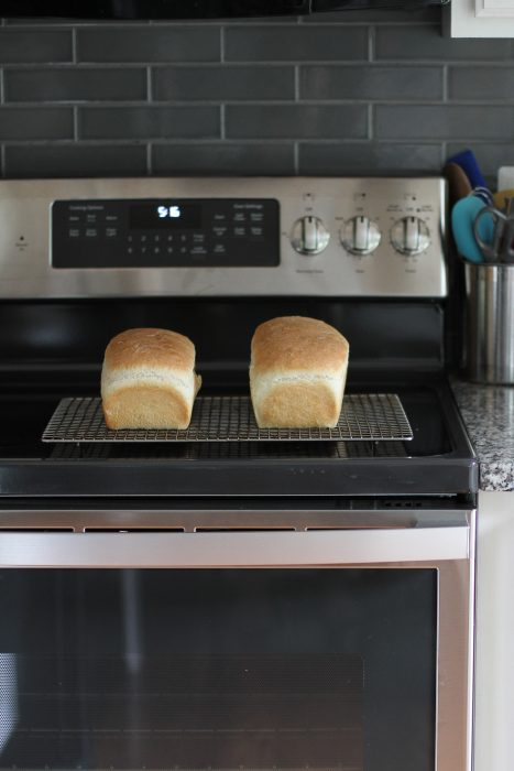 two loaves of white bread on a cooling rack