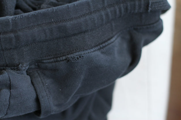waistband hole in a black pair of American Giant joggers.