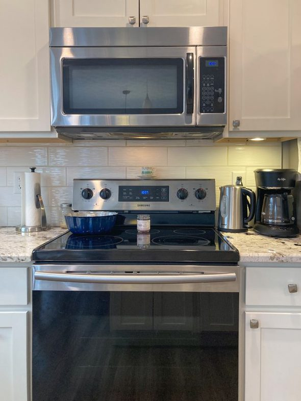 stove and microwave with white cabinets