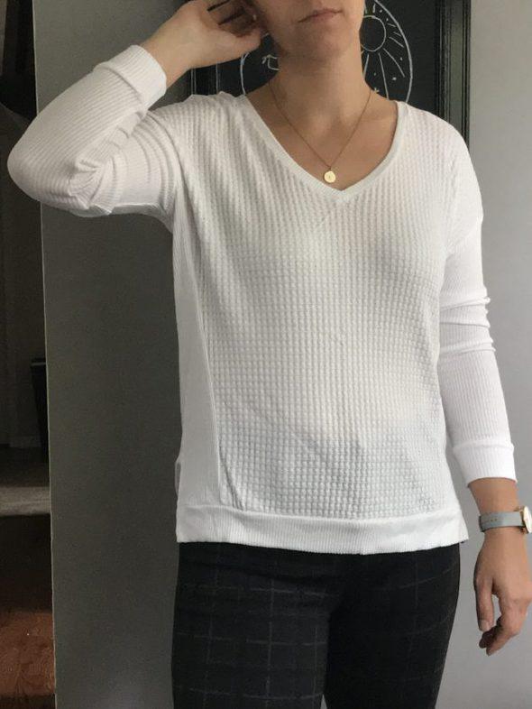 Kristen wearing a white v-neck shirt.