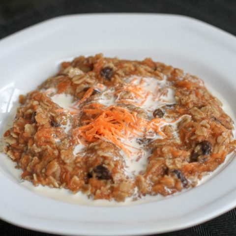 White bowl of oatmeal with carrots.