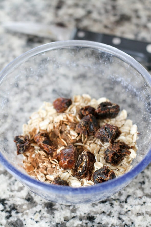 Dates in a bowl of uncooked oats