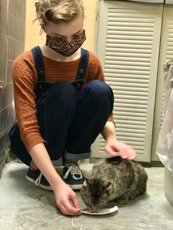 Sonia in overalls petting a cat.