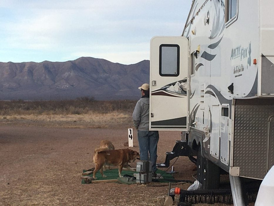 Cindy standing next to her fifth wheel camper.