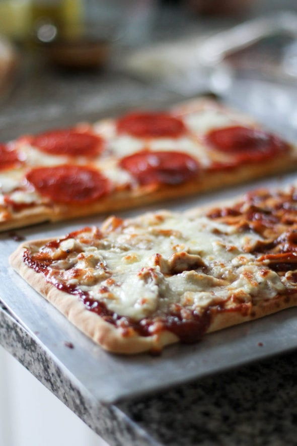 Two flatbread pizzas on a baking sheet.