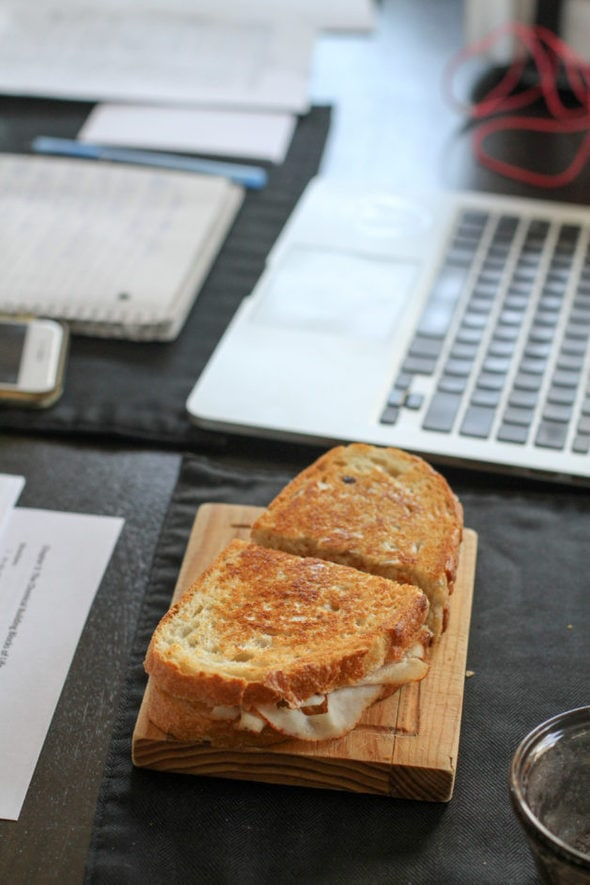 Panini on a plate next to a laptop.