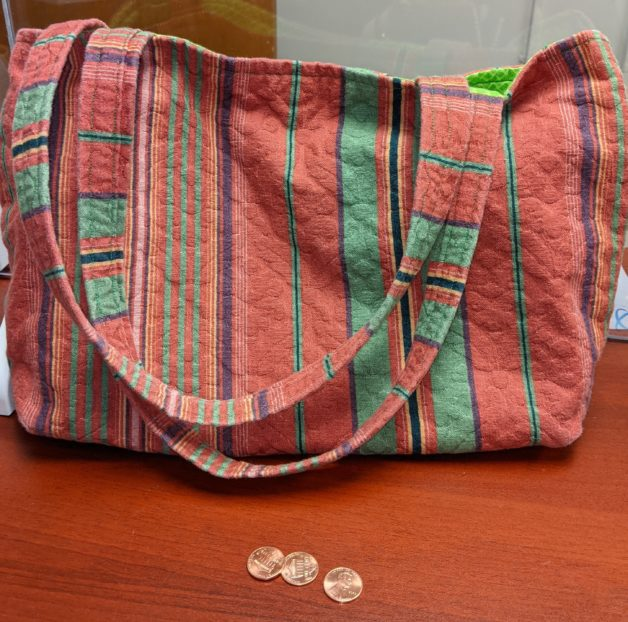 Red and orange homemade bag with handles.