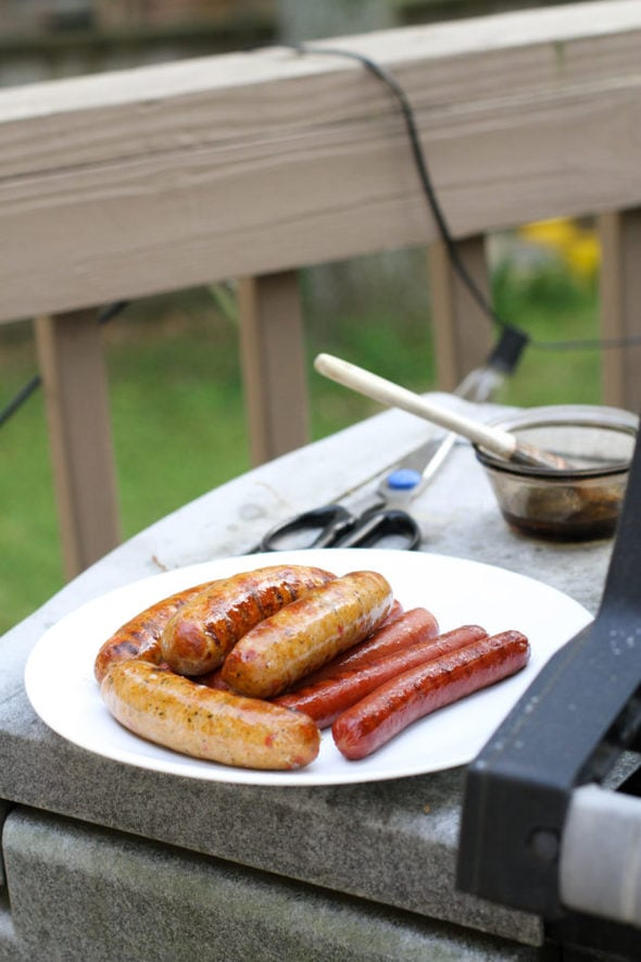 Grilled sausages and hot dogs on a plate next to a grill.