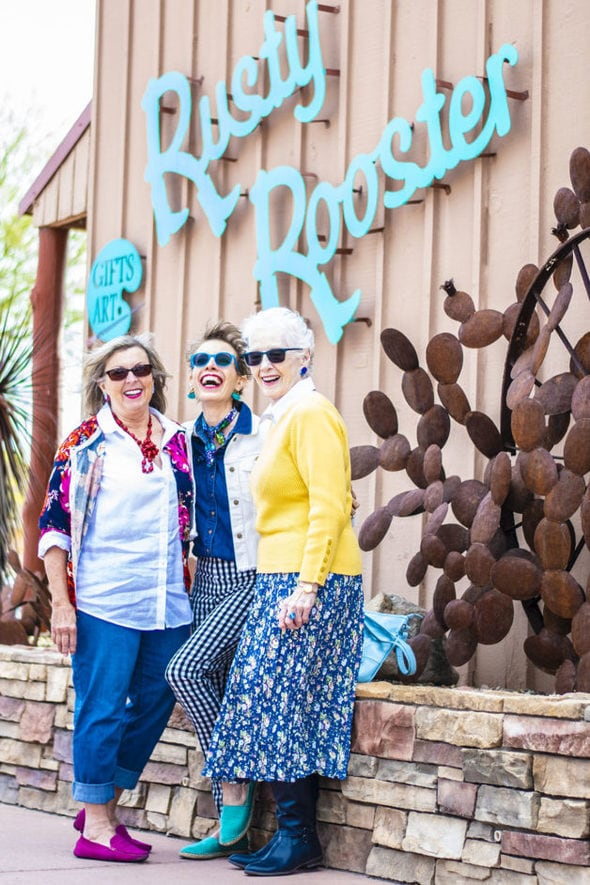 Three ladies with sunglasses on in front of a restaurant.