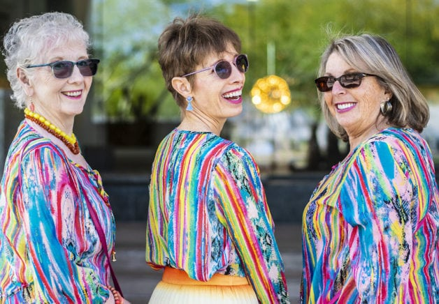 Three middle aged ladies in colorful striped shirts.