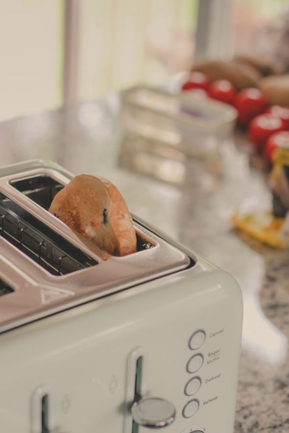 A bagel half in a light green toaster.