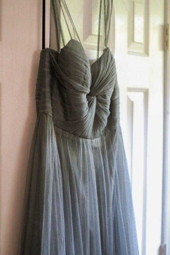 sage green bridesmaid dress hanging in a doorway.