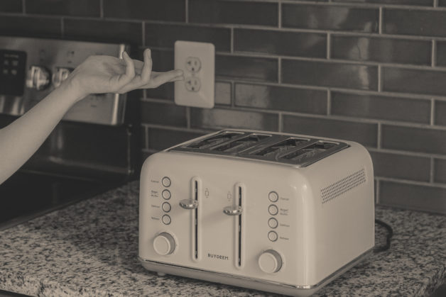 Buydeem Toaster on a countertop, black and white photo.