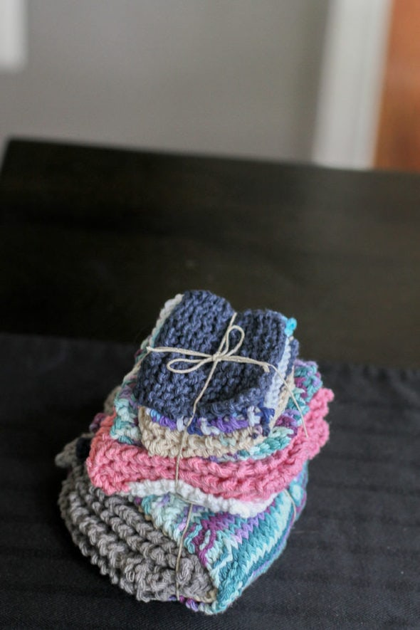 A stack of hand-knitted dishcloths, tied with a string.