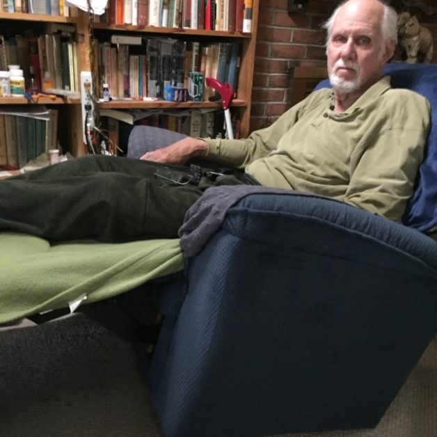 An older man sitting in a blue recliner. He has a white beard and white hair.