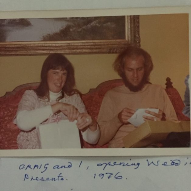 A newly married couple in the 1970s, sitting on a couch.