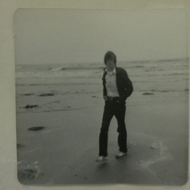 A black and white photo of a man walking on a beach.