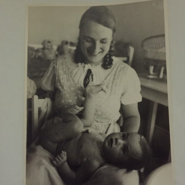 A black and white photo of a mother with a baby on her lap.
