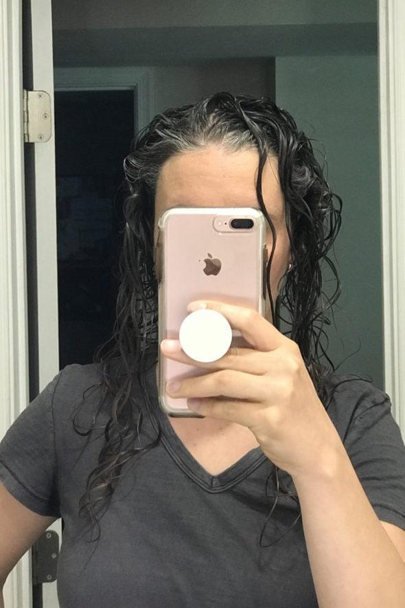 Kristen with wet, gelled hair, taking a mirror selfie.