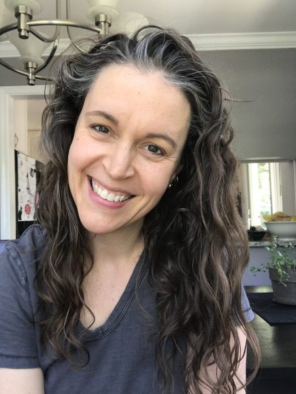 Kristen with wavy hair, smiling at the camera, wearing a gray shirt.