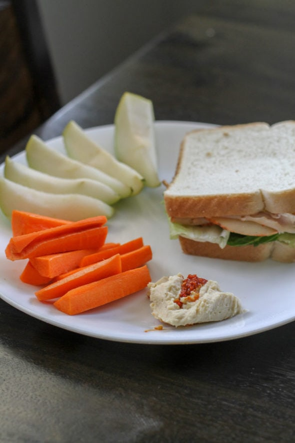 Turkey sandwich on a plate with produce and hummus.