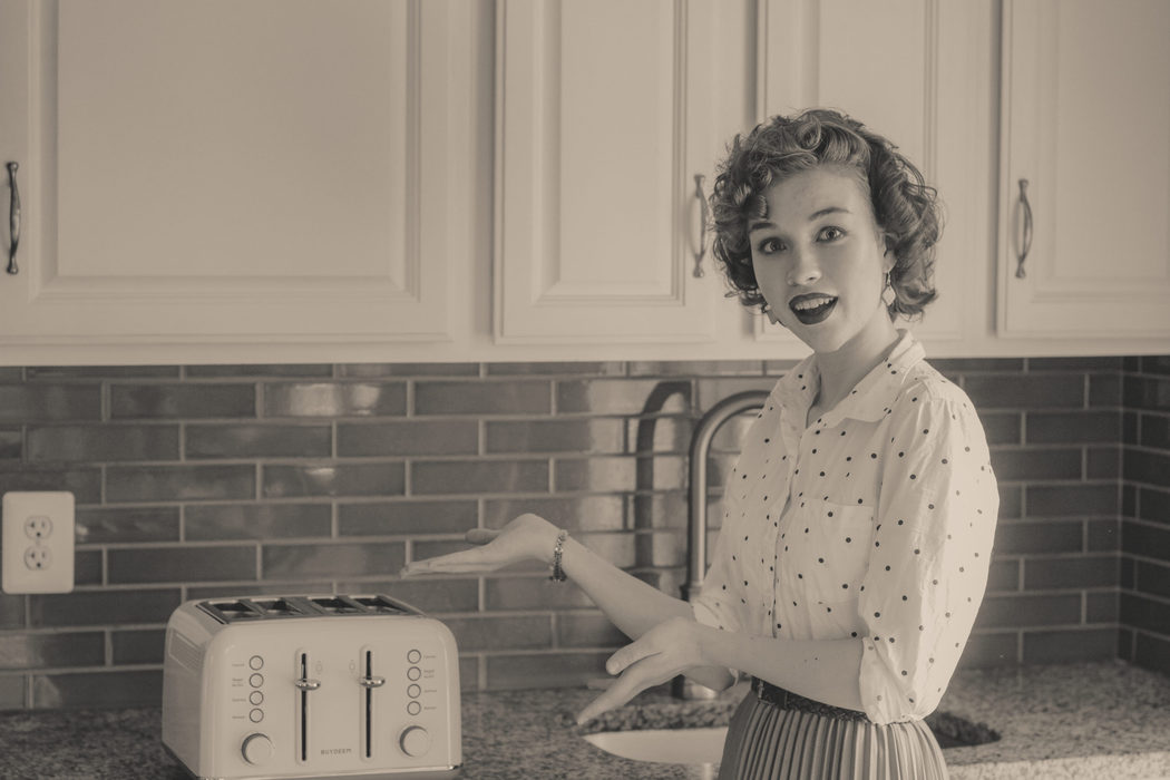 A black and white 1950s style photo of a curly-haired girl gesturing toward a toaster.