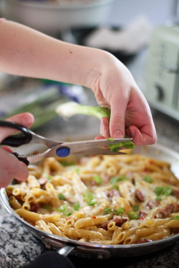 Sonia cutting green onions into a skillet of pasta.