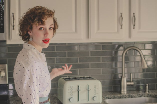 Sonia, looking retro, gesturing toward a green toaster.