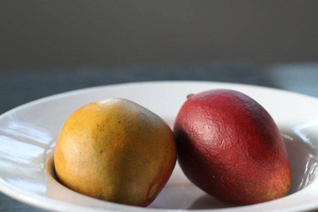 A red mango and yellow mango in a white bowl.