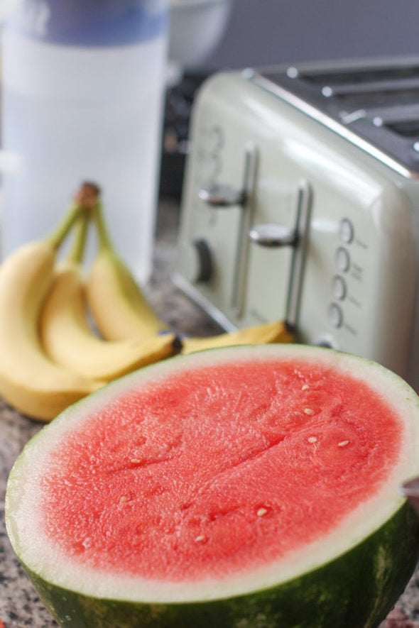 Half of a red watermelon, sitting on a counterop.