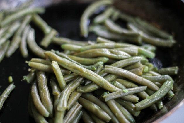 Frozen green beans in a skillet.