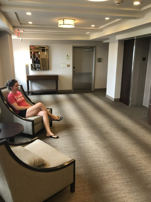 Kristen sitting in a chair in front of an elevator.