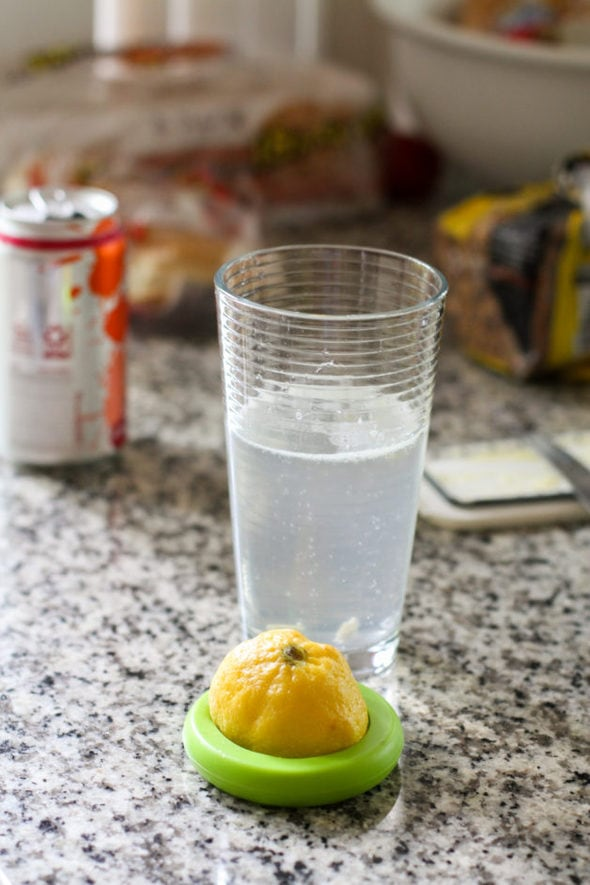 A glass of water with lemon juice in it.