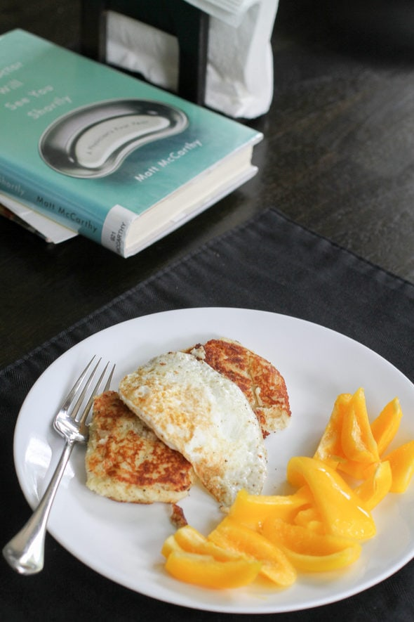 A white plate with potato cakes, fried egg, and yellow pepper slices.