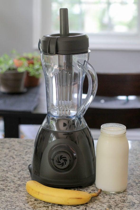 A Vitamix One blender with a banana and a glass jar of yogurt.