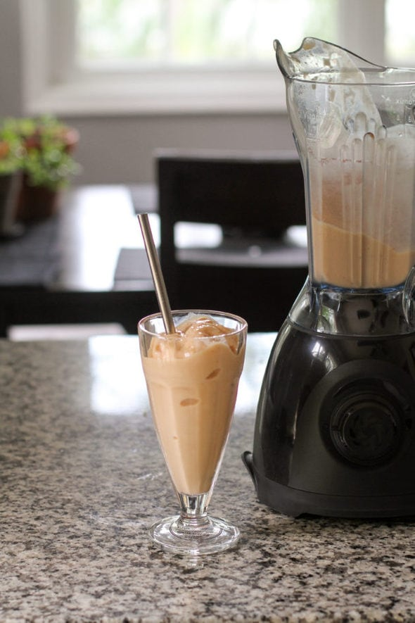 A peach smoothie in a soda fountain glass, next to a Vitamix One blender.