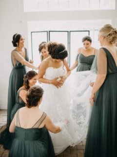 A group of bridesmaids helping a bride adjust her dress.