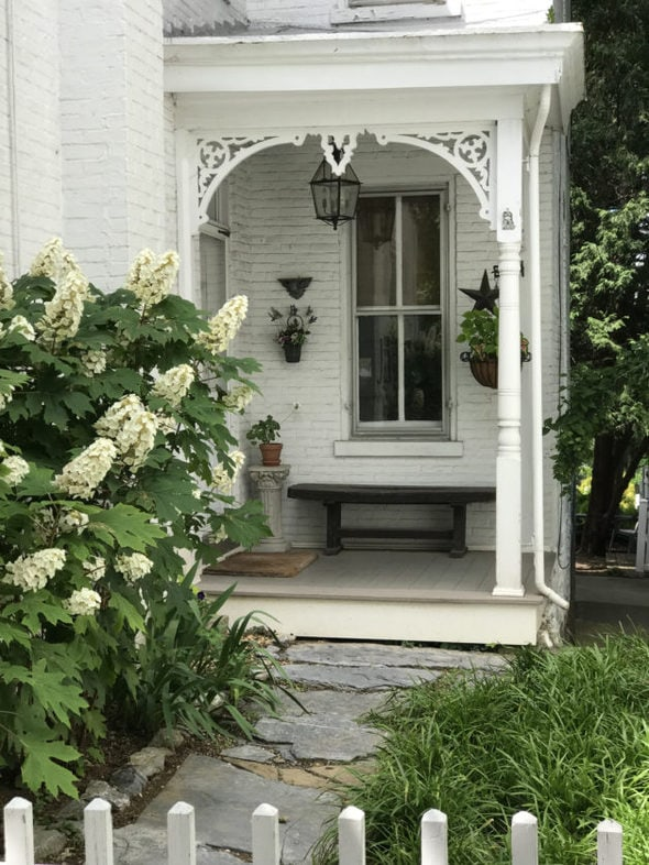 An old-fashioned white porch with bushes around it.