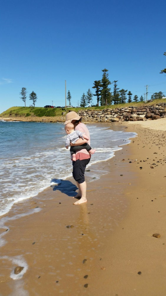 Emma with her child, standing on a beach.