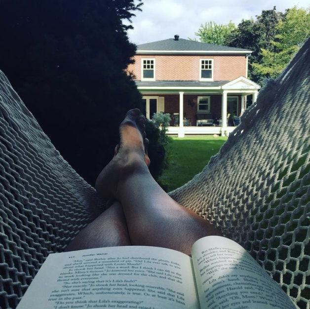 A view from a hammock with a book in a person's lap.