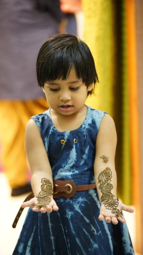 A little Indian girl looking at her arms.