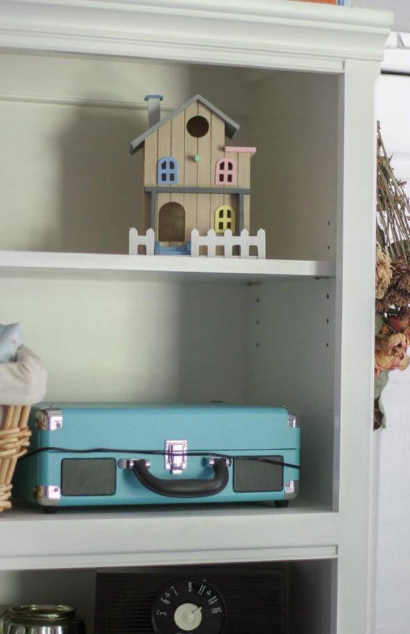 A white bookshelf with a birdhouse on the top shelf.