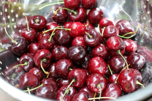 Cherries in a metal strainer.