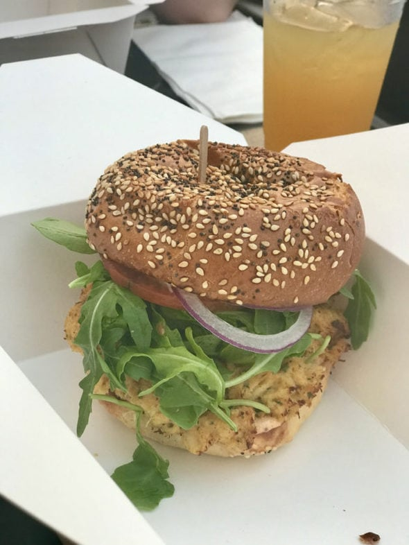 Crab cake sandwich with arugula and red onion.