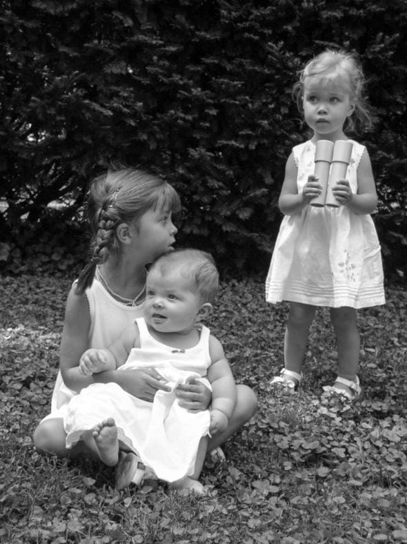 black and white of Lisey, Sonia, and Zoe in the grass.