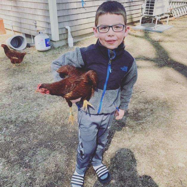 A boy holding a chicken.