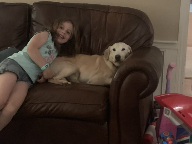 Barrie's daughter on the couch with their dog.