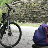 A bike in front of a railroad embankment.