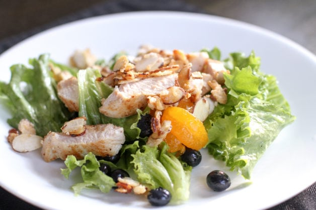 A green salad with chicken and fruit.