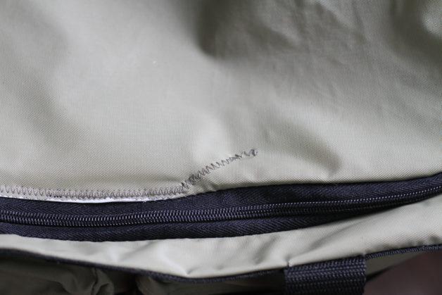 A zig-zagged rip repair on a taupe duffel bag.